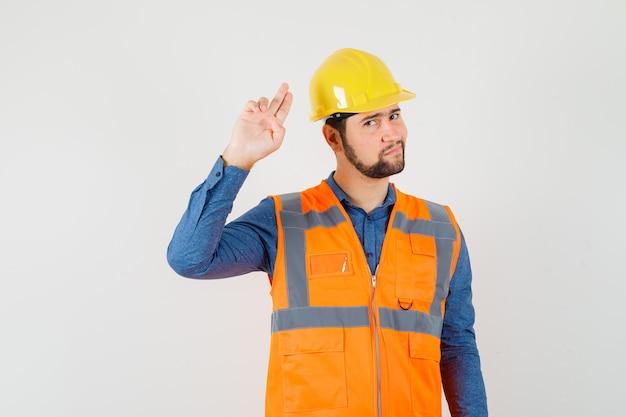 Jovem construtor gesticulando com a mão e os dedos na camisa