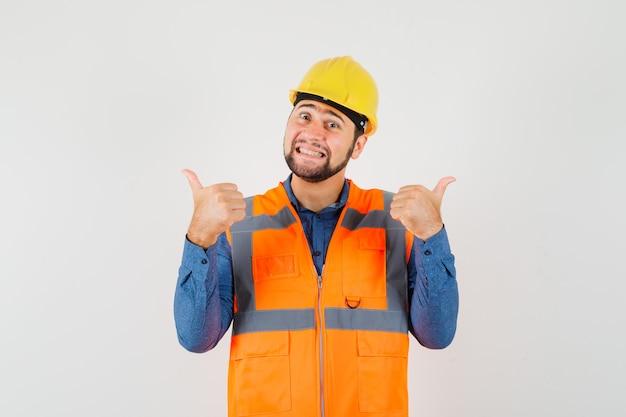 Jovem construtor mostrando dois polegares para cima na camisa, colete, capacete e olhando alegre, vista frontal.
