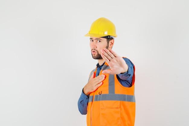 Jovem construtor mostrando gesto de parada na camisa, colete, capacete e parecendo decidido. vista frontal.