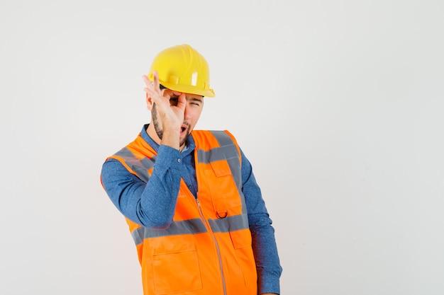 Jovem construtor mostrando sinal ok no olho na camisa, colete, capacete e olhando curioso, vista frontal.