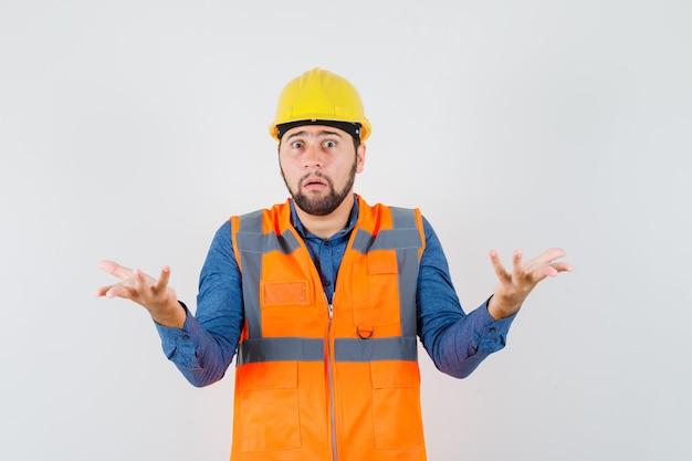 Jovem construtor mostrando um gesto desamparado na camisa, colete, capacete e parecendo confuso. vista frontal.
