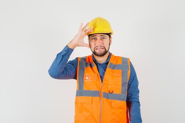 Jovem construtor na camisa, colete, capacete segurando a mão na cabeça e olhando triste, vista frontal.