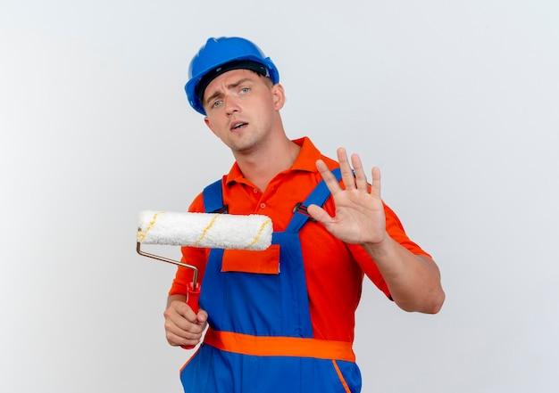 Jovem construtor preocupado com o uso de uniforme e capacete de segurança, segurando o rolo de pintura e mostrando um gesto de pare