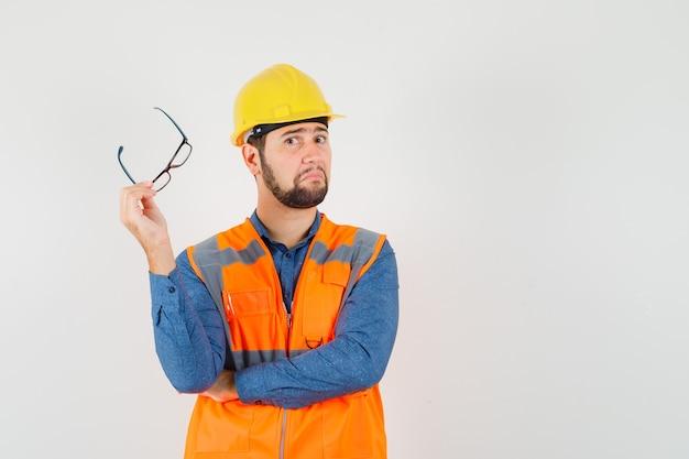 Jovem construtor segurando óculos na camisa
