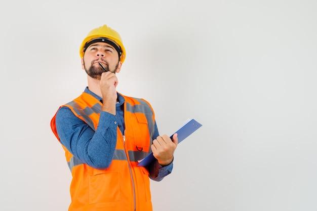 Jovem construtor segurando prancheta e caneta na camisa