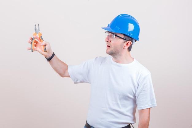 Jovem construtor segurando um alicate em uma camiseta, jeans, capacete e parecendo surpreso