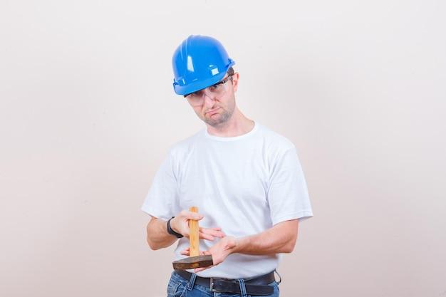 Jovem construtor segurando um martelo em uma camiseta, jeans, capacete e parecendo hesitante