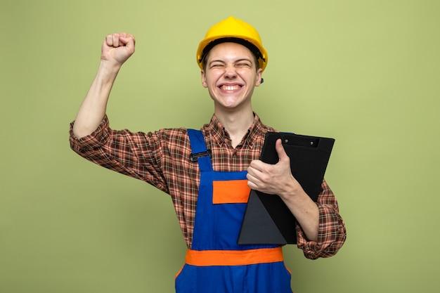 Jovem construtor segurando uma prancheta e vestindo uniforme isolado na parede verde oliva