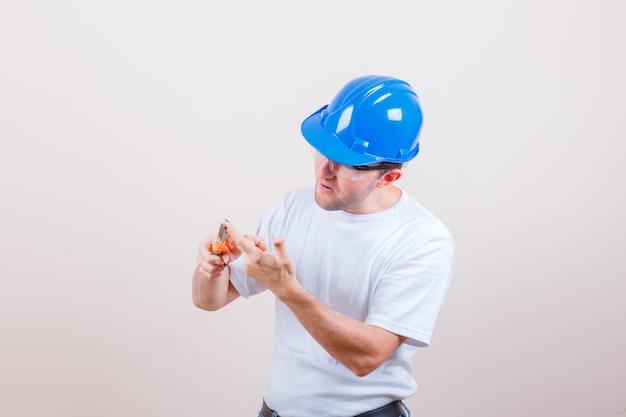 Jovem construtor tendo o dedo com um alicate na camiseta, capacete e olhando focado