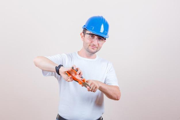 Jovem construtor tendo o dedo com um alicate na camiseta, capacete e parecendo divertido
