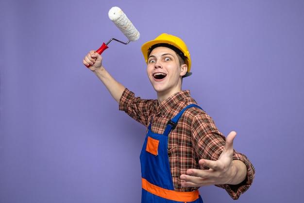 Jovem construtor usando uniforme, segurando a escova giratória isolada na parede roxa