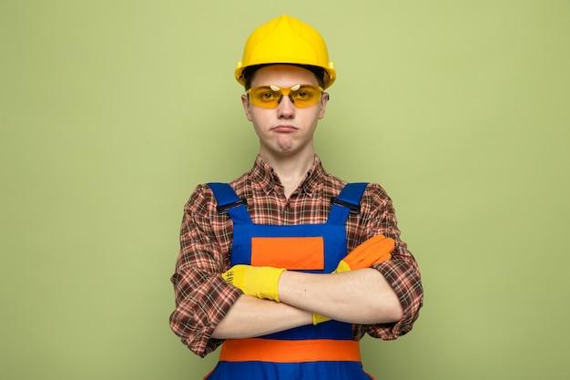 Jovem construtor vestindo uniforme e luvas com óculos isolados na parede verde oliva