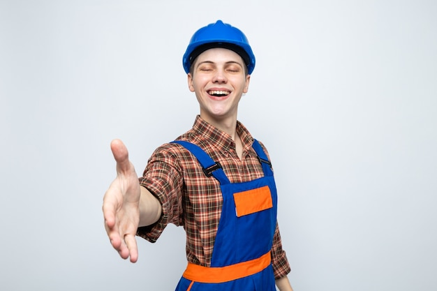 Jovem construtor vestindo uniforme isolado na parede branca