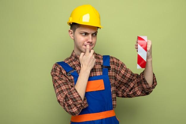 Jovem construtor vestindo uniforme segurando e olhando para fita adesiva isolada na parede verde oliva