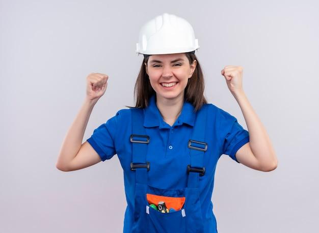 Jovem construtora alegre com capacete de segurança branco e uniforme azul com os punhos erguidos em um fundo branco isolado