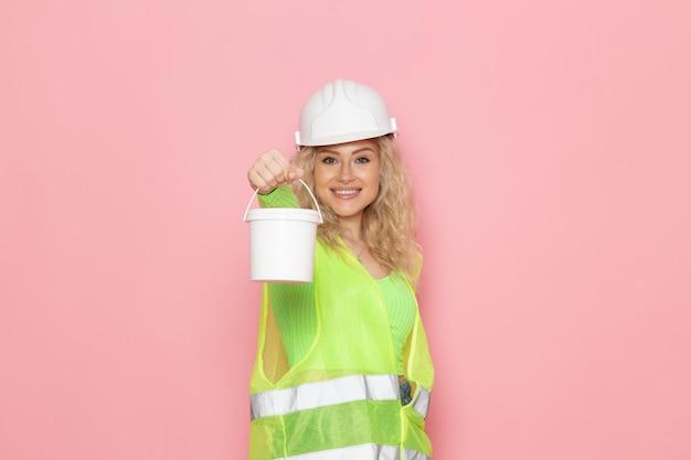 Jovem construtora com capacete de terno verde de construção segurando tinta branca no espaço rosa