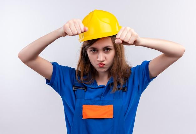 Jovem construtora com uniforme de construção e capacete de segurança cerrando os punhos olhando com o rosto carrancudo em pé sobre uma parede branca