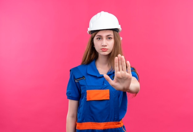 Jovem construtora com uniforme de construção e capacete de segurança em pé com a mão aberta, fazendo sinal de pare