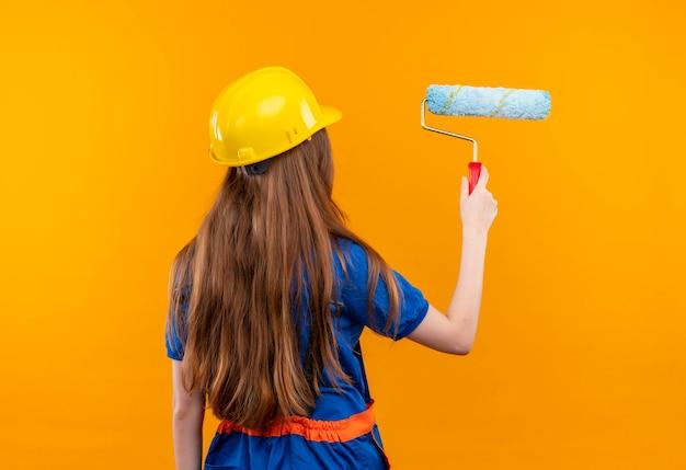 Jovem construtora com uniforme de construção e capacete de segurança em pé, de costas para pintar com rolo de pintura sobre a parede laranja