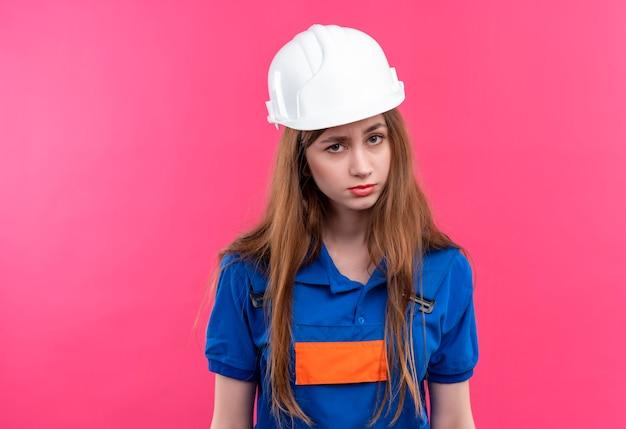 Jovem construtora com uniforme de construção e capacete de segurança, olhando com expressão cética em pé sobre a parede rosa