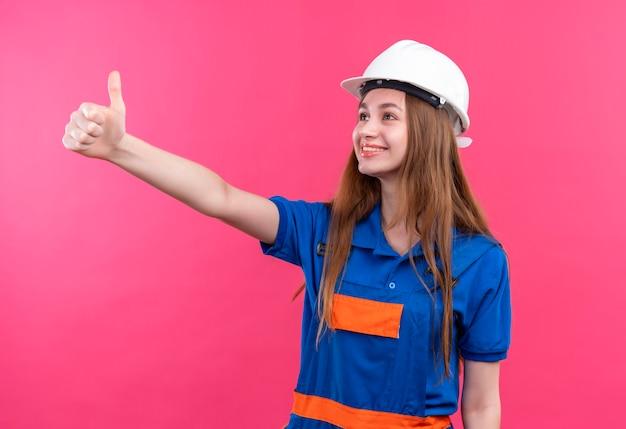 Jovem construtora com uniforme de construção e capacete de segurança olhando para o lado, sorrindo, mostrando os polegares em pé sobre a parede rosa