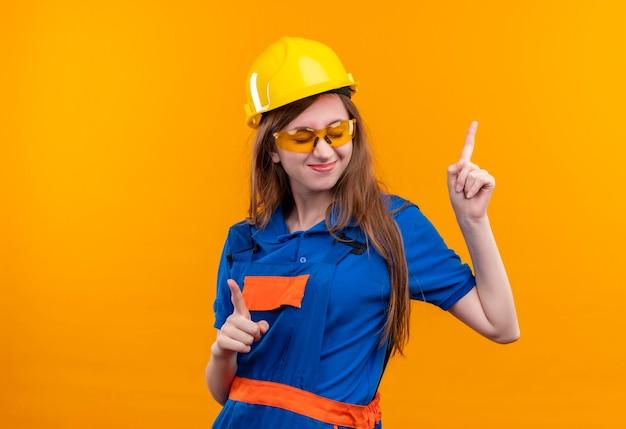 Jovem construtora com uniforme de construção e capacete de segurança se divertindo, sorrindo alegremente, apontando o dedo indicador para cima em pé sobre a parede laranja