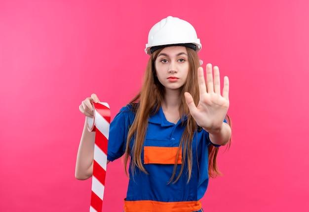 Jovem construtora com uniforme de construção e capacete de segurança segurando fita adesiva, fazendo sinal de pare com a mão em pé sobre a parede rosa