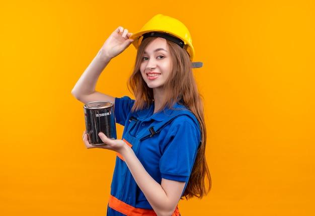 Jovem construtora com uniforme de construção e capacete de segurança segurando lata de tinta, parecendo confiante tocando seu capacete em pé sobre a parede laranja