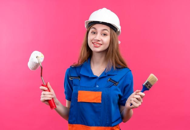 Jovem construtora com uniforme de construção e capacete de segurança segurando o pincel e o rolo de pintura, sorrindo amigável em pé sobre a parede rosa