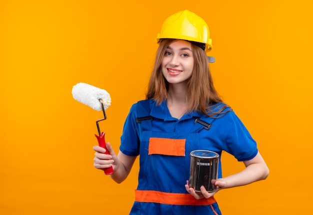 Jovem construtora com uniforme de construção e capacete de segurança segurando uma lata de tinta e um rolo sorrindo