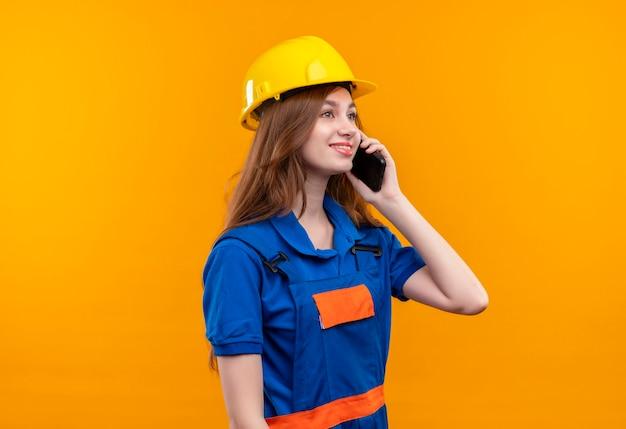 Jovem construtora com uniforme de construção e capacete de segurança, sorrindo enquanto fala no celular, em pé sobre a parede laranja