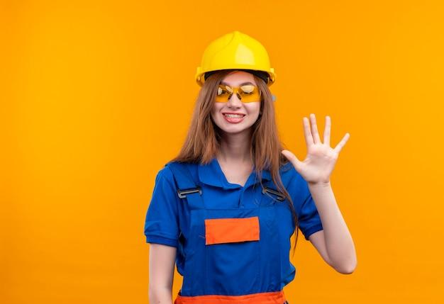 Jovem construtora com uniforme de construção e capacete de segurança sorrindo, mostrando e apontando para cima com os dedos número cinco em pé sobre a parede laranja