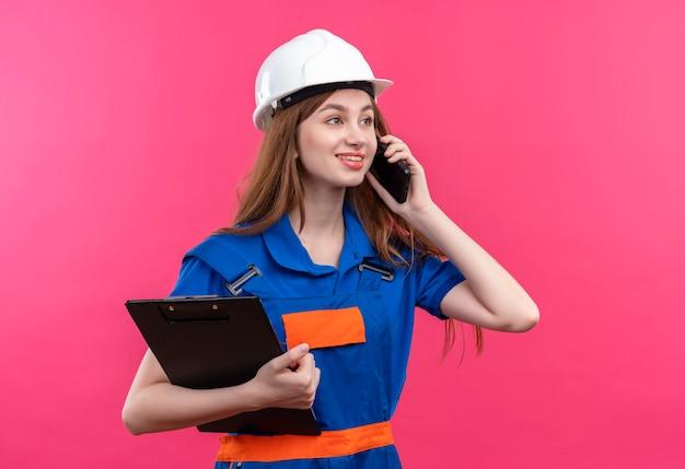 Jovem construtora com uniforme de construção e segurança segurando a prancheta, sorrindo enquanto fala no celular, em pé sobre a parede rosa