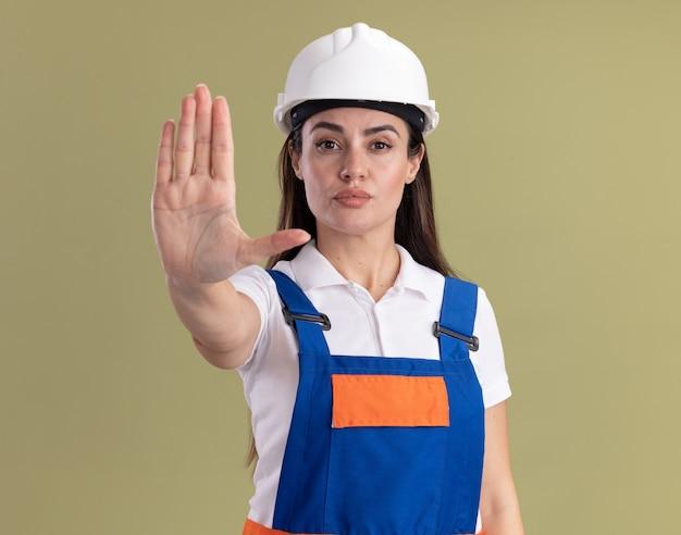 Jovem construtora confiante de uniforme, mostrando gesto de parada isolado na parede verde oliva