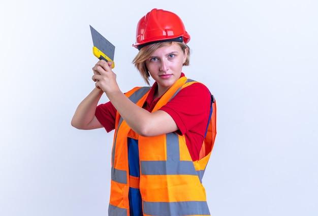 Jovem construtora confiante de uniforme segurando uma espátula isolada no fundo branco