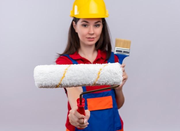 Jovem construtora confiante segurando rolo de pintura e pincel no fundo branco isolado