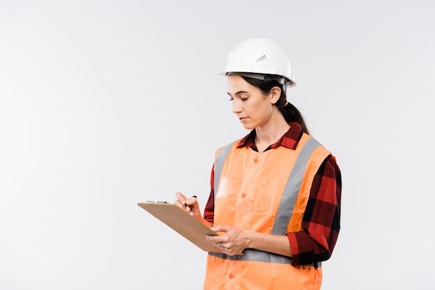 Jovem construtora de capacete, flanela e colete de trabalho, fazendo anotações em um documento na frente da câmera, isolada