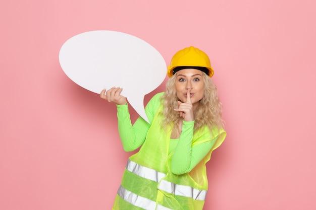 Jovem construtora de frente para o capacete com um terno de construção verde segurando uma placa branca de silêncio no espaço rosa