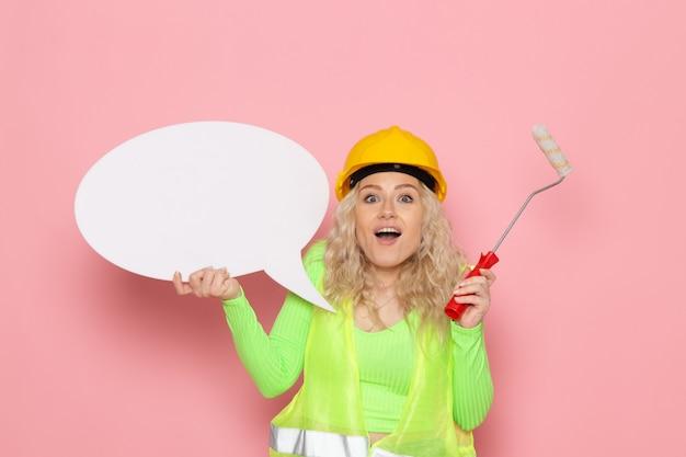 Jovem construtora de frente para o capacete com um terno de construção verde segurando uma placa branca e escovar com um sorriso no espaço rosa