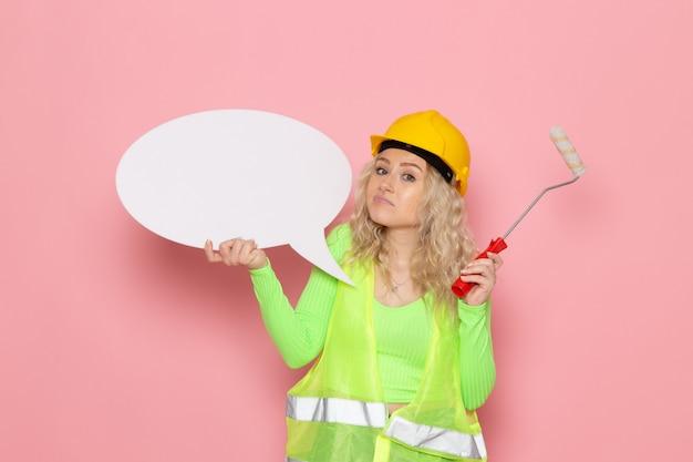 Jovem construtora de frente para o capacete com um terno de construção verde segurando uma placa branca e uma escova no espaço rosa