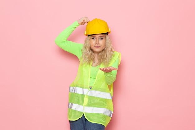 Jovem construtora de frente para o capacete de terno de construção verde simplesmente posando na senhora do trabalho de construção de arquitetura de espaço rosa