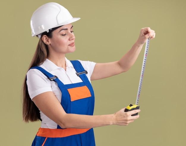 Jovem construtora impressionada de uniforme esticando a fita métrica isolada na parede verde oliva