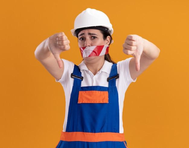 Jovem construtora insatisfeita de uniforme com a boca fechada e fita adesiva mostrando os polegares para baixo, isolados na parede laranja