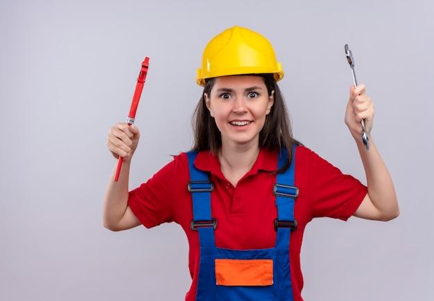 Jovem construtora irritada segurando uma chave inglesa e uma chave de oficina em um fundo branco isolado com espaço de cópia