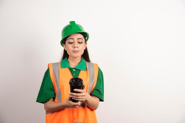 Jovem construtora olhando na xícara preta. foto de alta qualidade