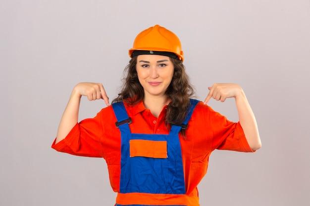 Jovem construtora orgulhosa com uniforme de construção e capacete de segurança, parecendo confiante, apontando para si mesma sobre um fundo branco isolado