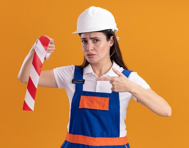 Jovem construtora rigorosa com uniforme segurando e aponta para fita adesiva isolada na parede laranja