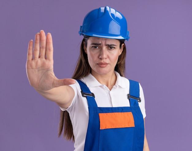 Jovem construtora rigorosa de uniforme mostrando gesto de parada isolado na parede roxa