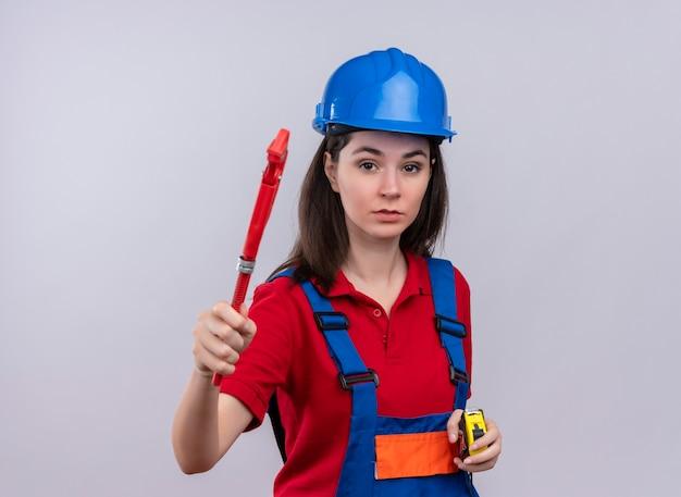Jovem construtora segurando uma chave inglesa e uma fita métrica em um fundo branco isolado com espaço de cópia