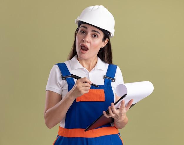 Jovem construtora surpresa de uniforme segurando uma prancheta com uma caneta isolada na parede verde oliva